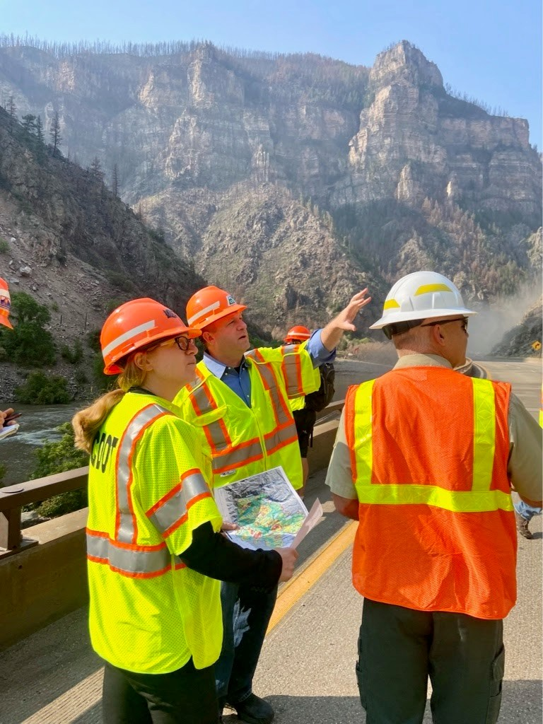 Governor Polis, CDOT Director Shoshana Lew, and a US Forest Service representative observe the damage on Interstate 70 in Glenwood Canyon.