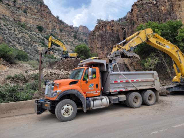 CDOT crews clean up debris in Glenwood canyon with heavy equipment.